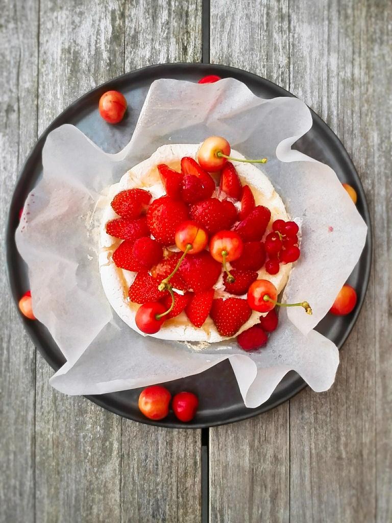 pavlova met rode bessen, gepimpt met witbuiken uit de tuin